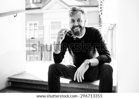 Full beard man is sitting on the steps of ancient house in front of the terrace or balcony in the old city. He is holding his sun glasses and smiling in the camera. Black and white photography. - stock photo