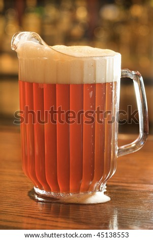 Full beer pitcher with foam on a bar counter. Vertical shot. - stock photo