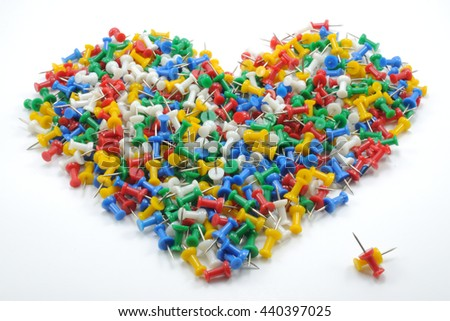 Full big heart shape of colorful push pins isolated on white background. Two pins are separated at the bottom right.