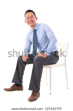 Full body Asian business man sitting on a chair over white background - stock photo