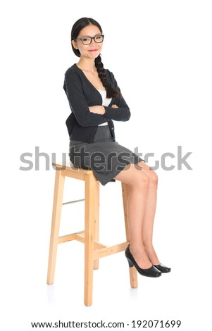Full body Asian business woman seated on chair, arms crossed isolated on white background. Chinese girl model. - stock photo