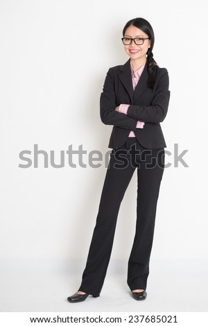 Full body Asian business woman smiling and standing on plain background. - stock photo