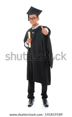 Full body Asian male university student in graduation gown thumb up isolated on white background