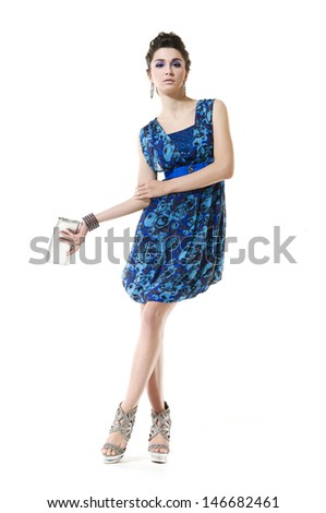 Full body fashion girl holding little purse posing in the studio