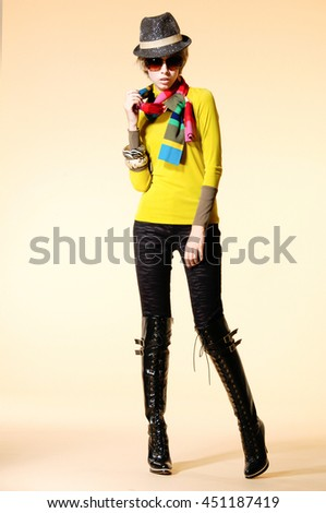 Full body fashion model in fashion clothes with,hat,posing on light background - stock photo