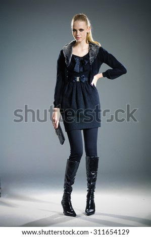 Full body fashion model in fashion dress posing in light background - stock photo