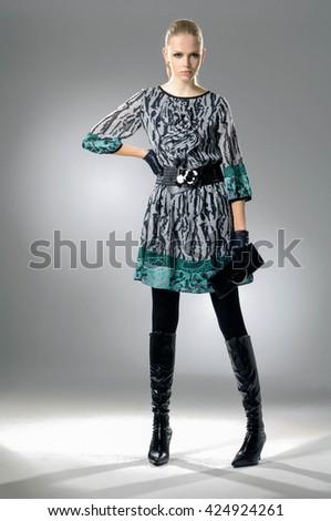 Full body fashion model in fashion dress posing in light background - stock photo