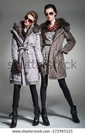 Full body fashion model in fur coat clothes posing-gray background  - stock photo