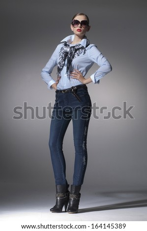 Full body fashion model in jeans with sunglasses posing