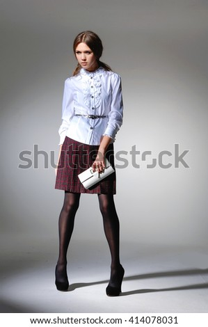 Full body fashion model in modern clothes with purse posing -light background