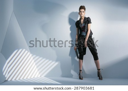Full body fashion model wearing modern cloth holding purse posing - stock photo