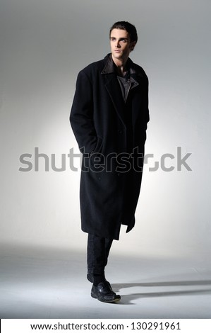 Full body Fashion Shot of a young man in coat on light background