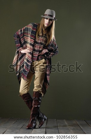 full body fashion woman in hat posing wooden floor