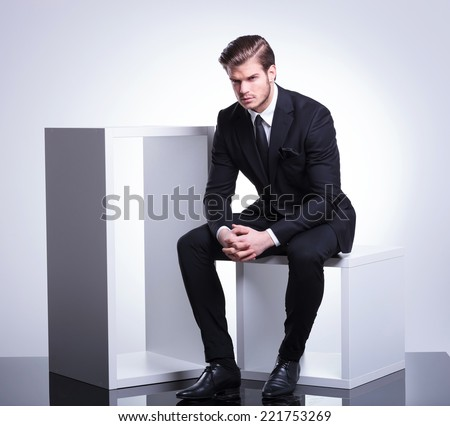 Full body image of a handsome young business man sitting on a white cube holding his hand together, looking at the camera. - stock photo