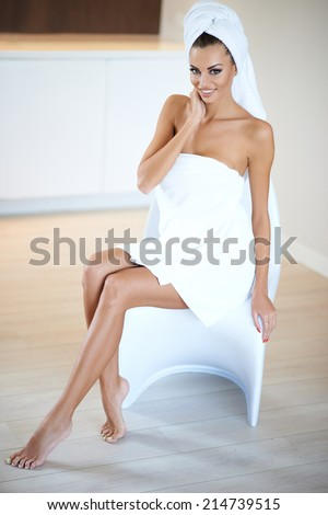 Full Body Image of Smiling Woman Wearing White Bath Towel Sitting on Chair - stock photo