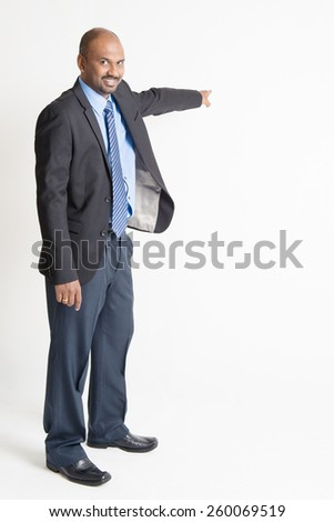 Full body Indian businessman pointing away to copy space, on plain background.