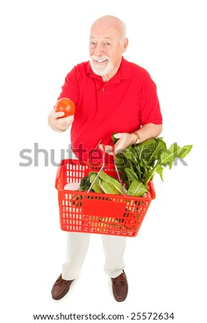 Full body isolated view of a senior man grocery shopping and holding out a fresh tomato. - stock photo