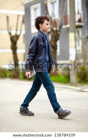 Full body length of a teenager walking - stock photo