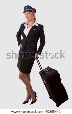 Full body of a blond caucasian woman wearing flight attendant hat and suit holding on to a suitcase over white