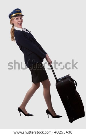Full body of a blond caucasian woman wearing flight attendant hat and suit pulling on a heavy suitcase over white