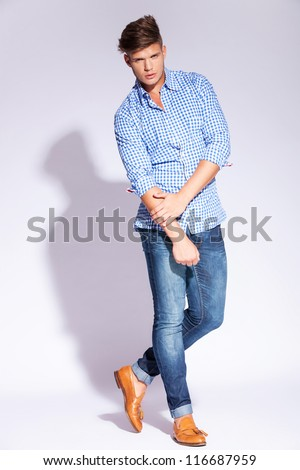 full body of a fashion young man posing on gray background - stock photo