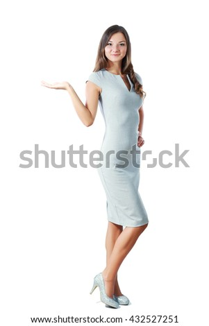 Full body of a standing woman in grey dress pointing at side isolated on a white background  - stock photo