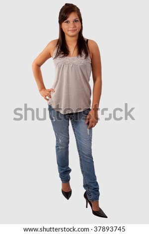 Full body of a young attractive brunette teen wearing high heels and jeans standing over white - stock photo