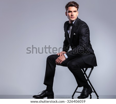 Full body of a young business man sitting on a chair while looking away from the camera. - stock photo