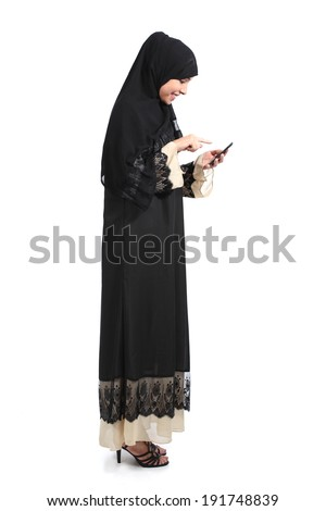 Full body of an arab saudi woman browsing a smart phone isolated on a white background                - stock photo