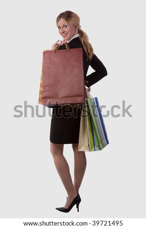 Full body of an attractive blond woman in a skirt business attire smiling and holding in some shopping bags over white