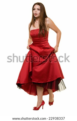 Full body of an attractive young brunette woman wearing a long formal red satin gown holding up showing cute red shoes