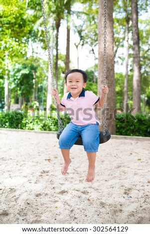 Full body of asian boy swinging. Small child playing on colorful swing in a sunny playground or family park - stock photo