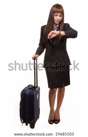 Full body of Asian woman in black business suit skirt with suitcase looking at wrist watch - stock photo