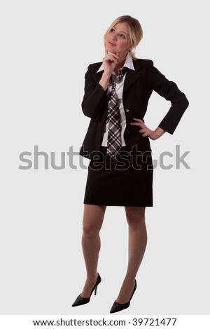 Full body of attractive blond woman with long legs wearing business suit skirt and tie standing on white with hand on chin looking up thinking