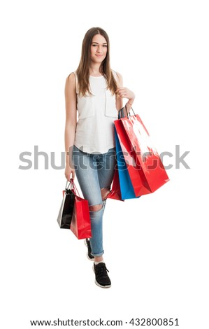 Full body of attractive young shopaholic holding many shopping bags and smiling isolated on white background - stock photo