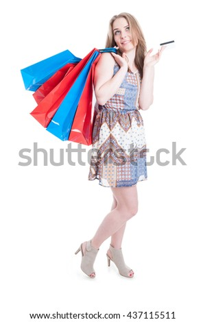 Full body of attractive young woman holding debit card and big colored shopping bags isolated on white background - stock photo