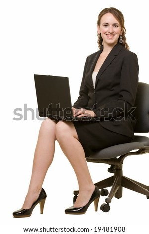 Full body of brunette caucasian woman wearing business skirt suit sitting holding laptop on knees over white smiling