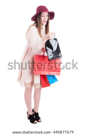 Full body of curious young shopaholic carrying shopping bags and looking inside black one isolated on white with copyspace - stock photo