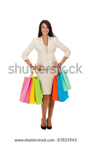 Full body of tall young brunette woman in professional business suit standing holding colorful shopping bags in hands isolated over white background.