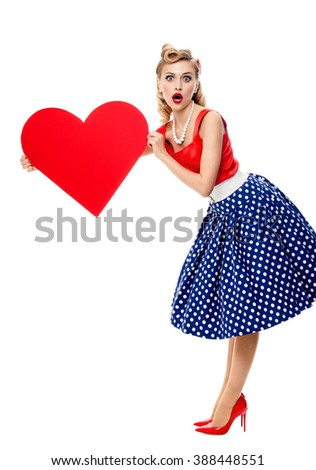 Full body of woman holding heart symbol, dressed in pin-up style dress with polka dot, isolated over white background. Caucasian blond model posing in retro fashion and vintage concept studio shoot.