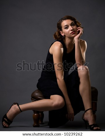 Full body of young pretty brunette woman modeling long black dress while sitting on a stool looking bored on grey background