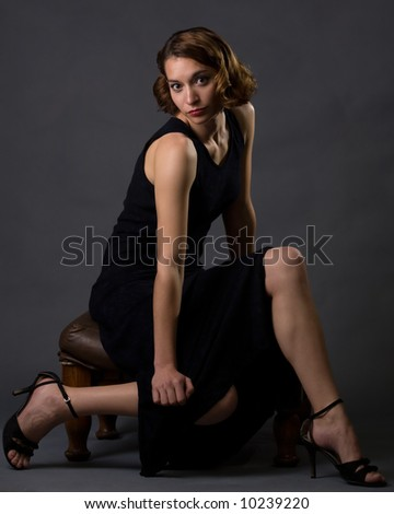 Full body of young pretty brunette woman modeling long black dress while sitting on a stool on grey background