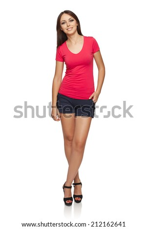 Full body of young woman in bright red top and shorts standing relaxed with hand in pocket, over white studio background - stock photo