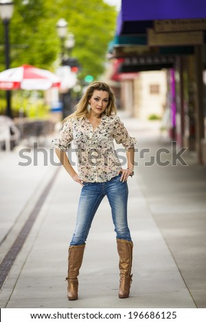 Full body photo of a young lady in tall boots and jeans posing downtown