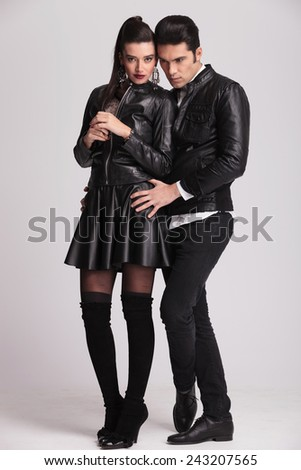 Full body picture of a beautiful brunette posing on grey studio background while her boyfriend is holding her.