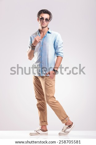 Full body picture of a casual fashion man stepping forward while fixing his collar. - stock photo