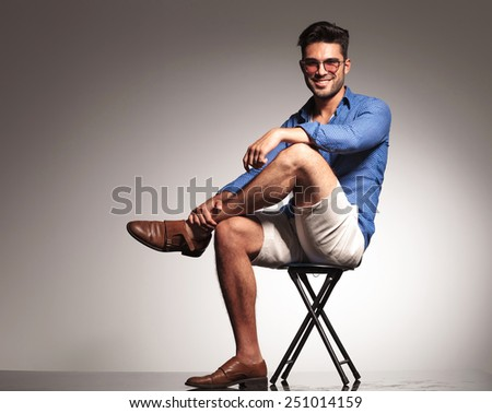 Full body picture of a casual young fashion man sitting with his legs crossed, smiling at the camera. - stock photo