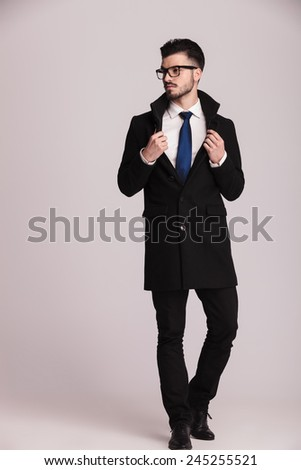 Full body picture of a elegant business man looking away from the camera while pulling his collar. - stock photo