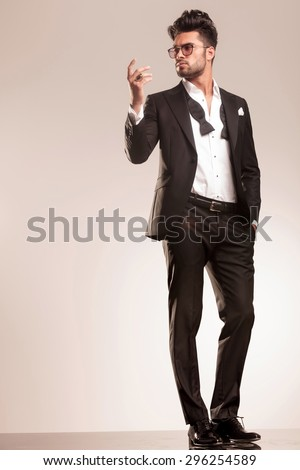 Full body picture of a elegant business man standing on grey studio background, holding one hand in his pocket and the other one up. - stock photo