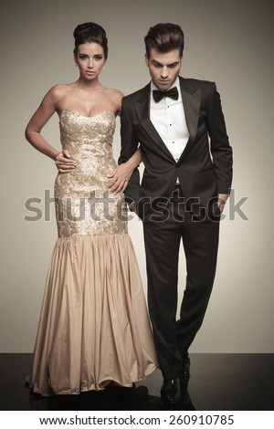 Full body picture of a elegant couple walking on studio background. The man is looking down while holding both hands in his pockets. - stock photo